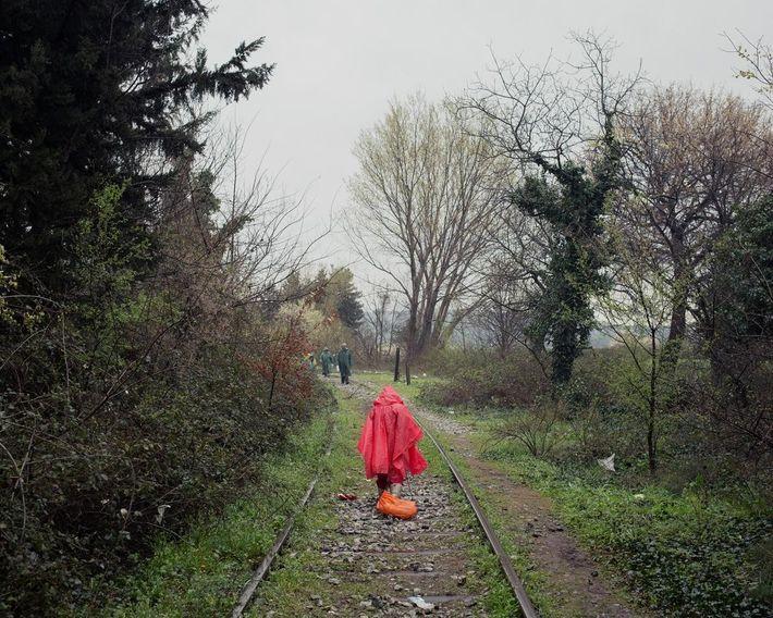 Una niña pequeña recoge pedacitos de madera en las vías del tren. Lo que lleve a ...