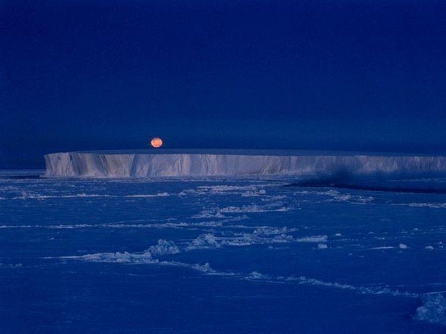 La luna sobresale de un gigantesco icerberg en la Antarctica.Este Mar, es el hogar de muchos …