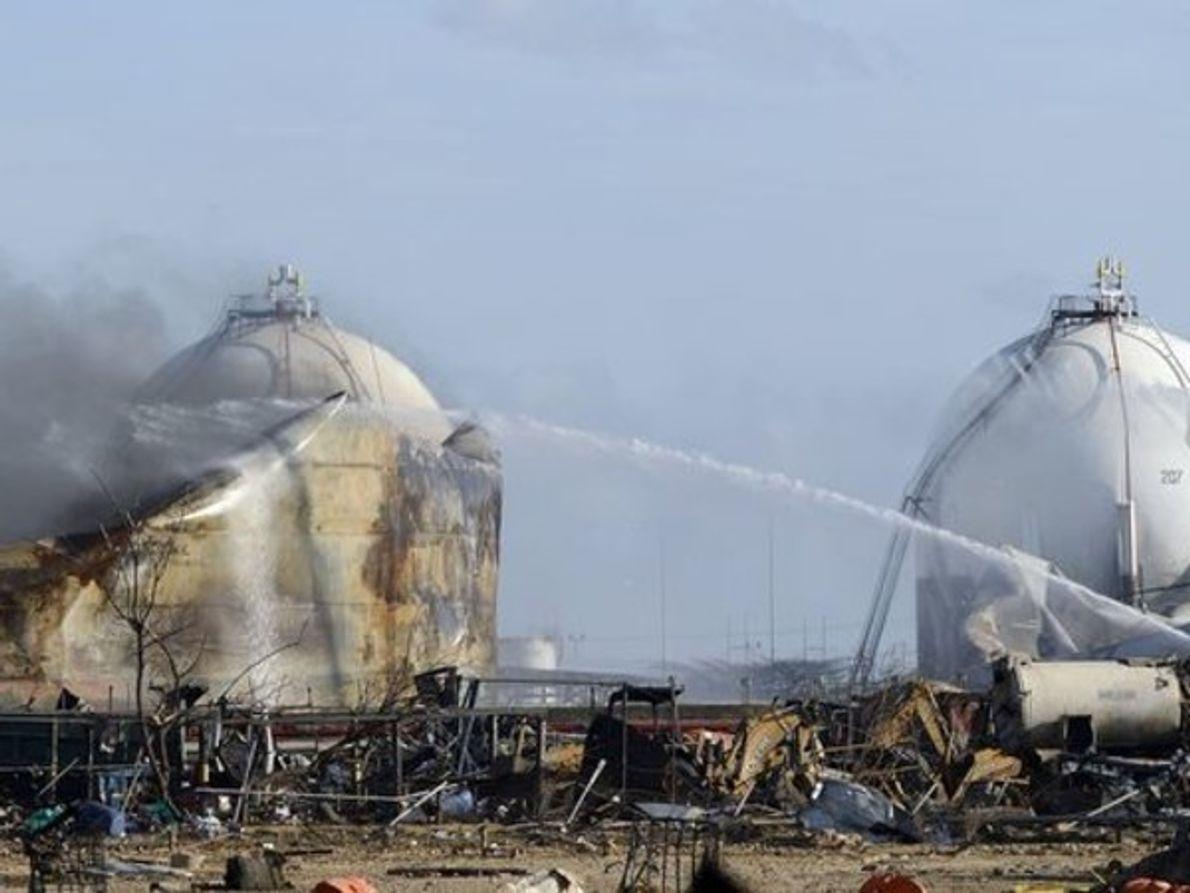 Los bomberos limpian con mangueras los tanques de almacenamiento de petróleo en la refinería Amuay el …