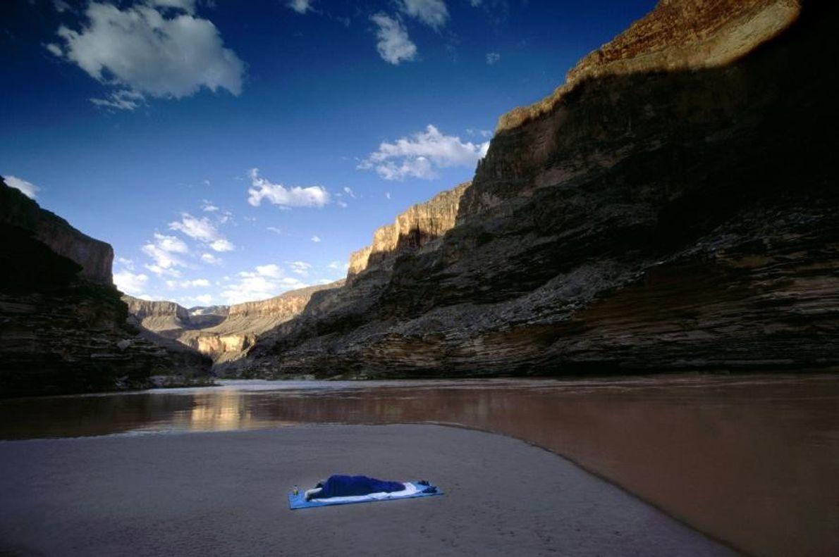Un viajero solitario duerme en un banco de arena del río Colorado, en el Gran Cañón.