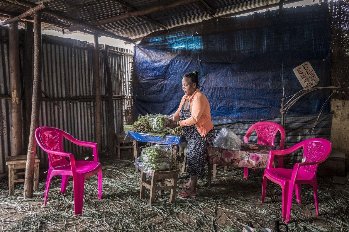 Una mujer escoge hojas de khat