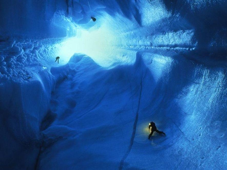 Espeleólogos haciendo rappel en una placa de hielo de 90 metros en Groenlandia. Las cuevas glaciares ...