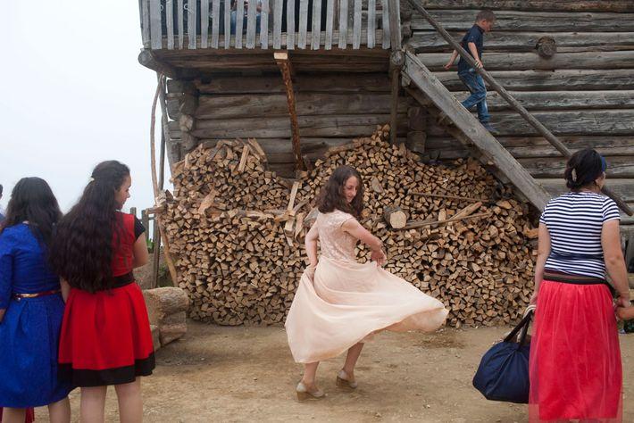 Imagen de una niña  dando vueltas con su vestido rosa frente a la leña.