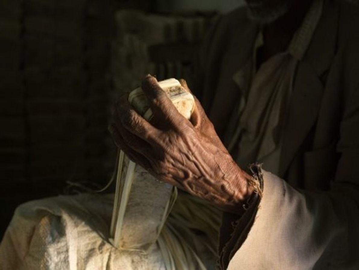 Las pilas de barras de sal rodean a un hombre en Mekele, Etiopía. Esta …