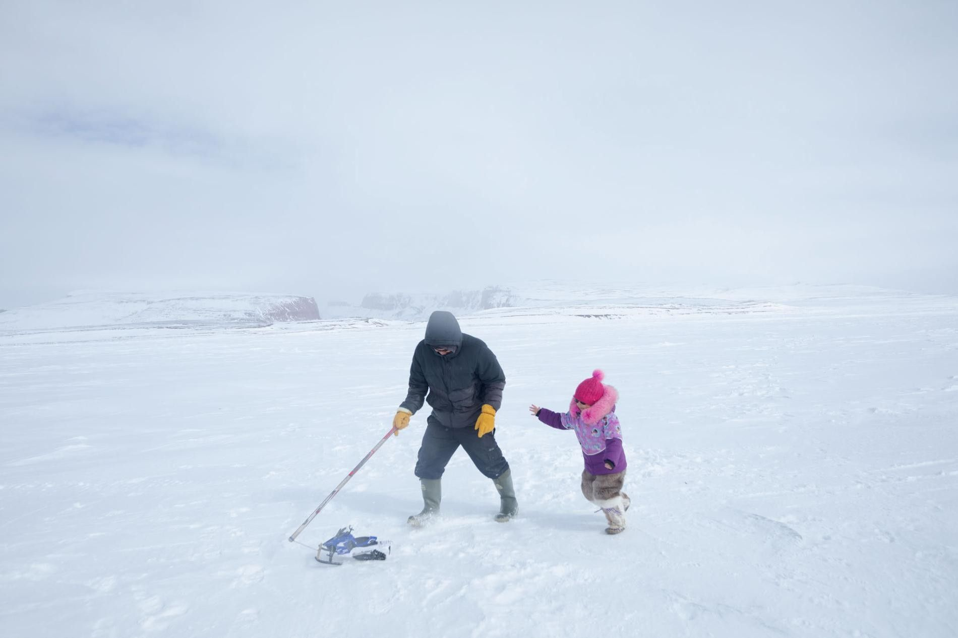 Darcy Enoogoo tira de una moto de nieve de juguete junto a su hija, Alana, durante ...