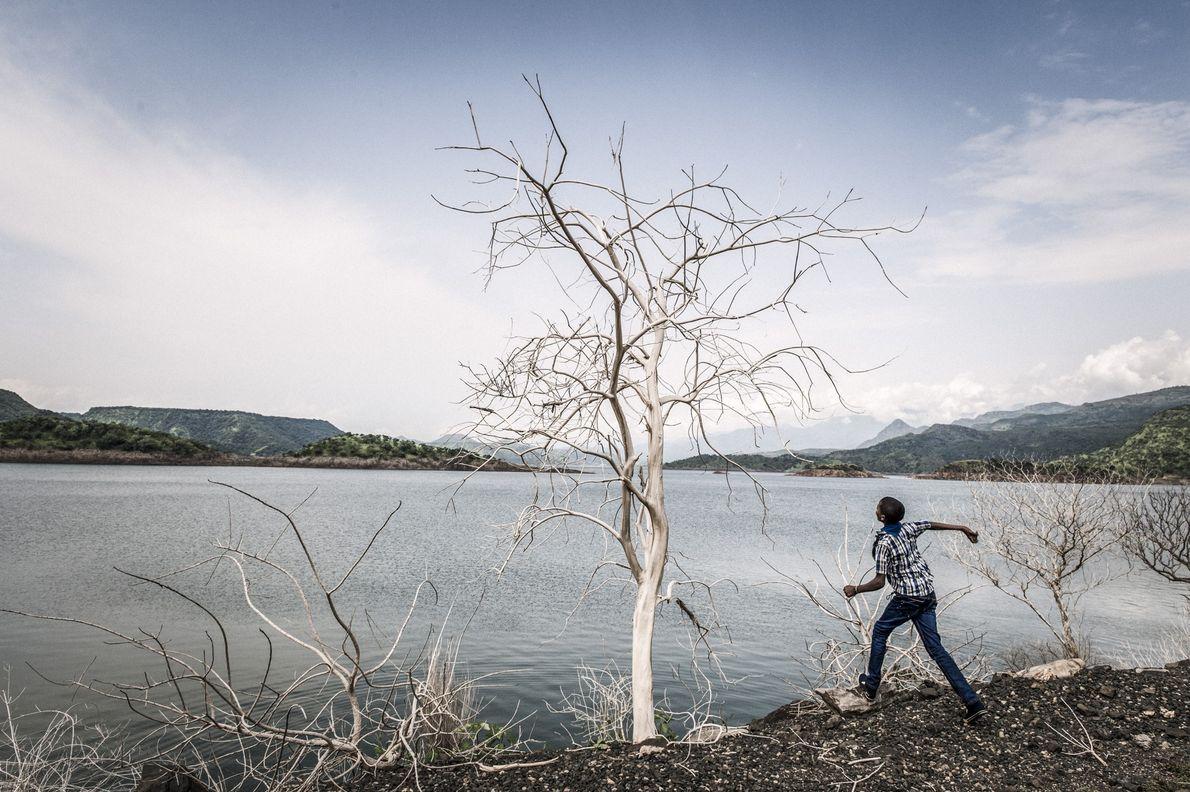 Un niño tira piedras en un lago artificial