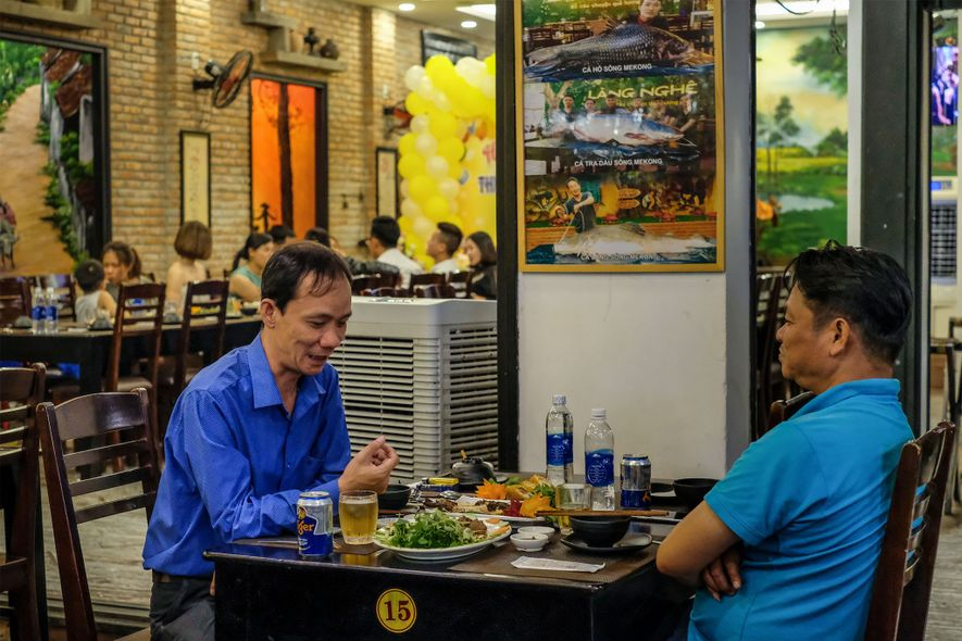 En el restaurante Lang Nghe, en Danang, Vietnam, los clientes cenan bajo un cartel que oferta carpas siamesas y peces gato gigantes de más de 136 kilogramos.