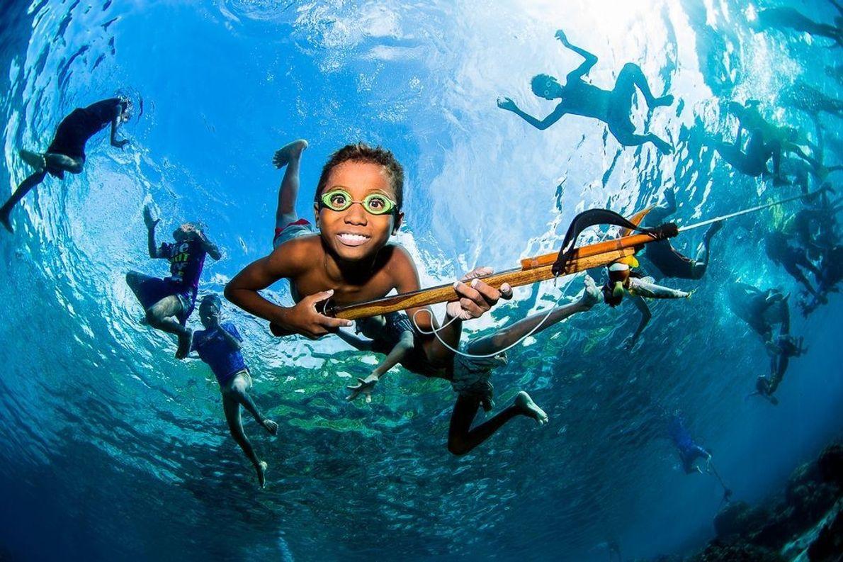 Niños pescando bajo el agua en Alor