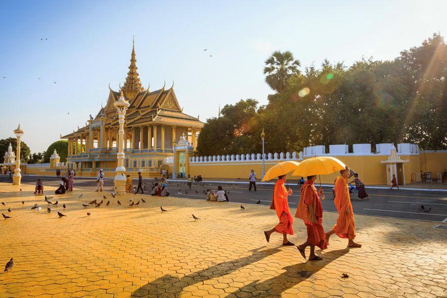 Los monjes budistas pasan frente al palacio real de Phnom Penh, Camboya.