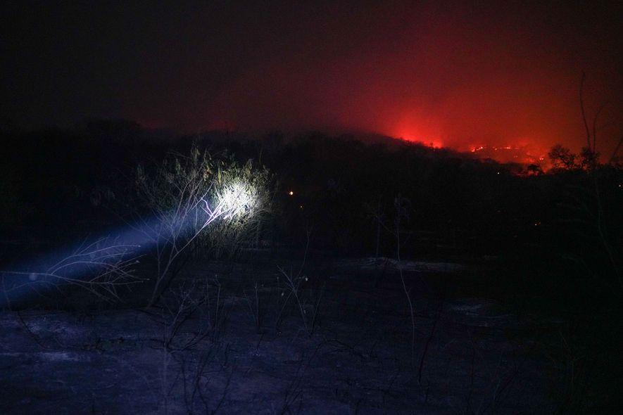 Los bomberos voluntarios de la comunidad de Roboré alumbran el camino mientras se desplazan por el ...
