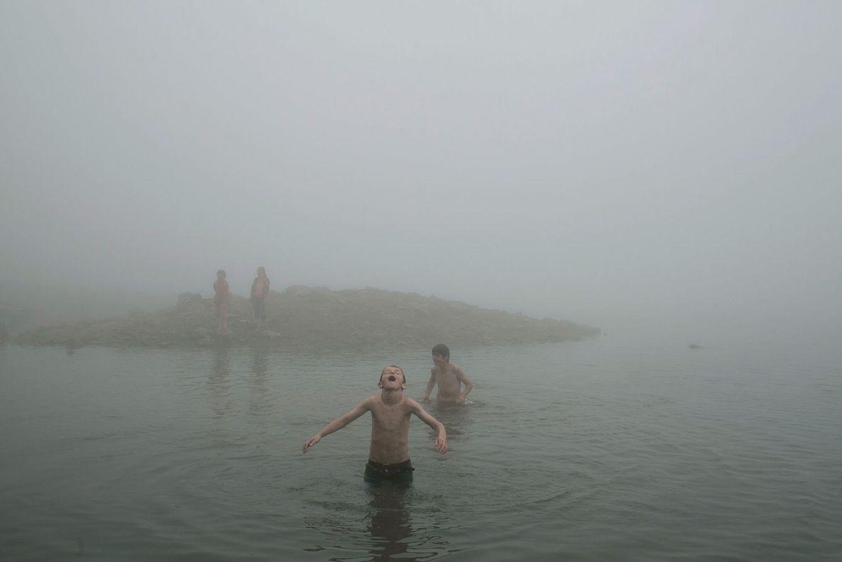 Imagen de unos niños jugando en un lago