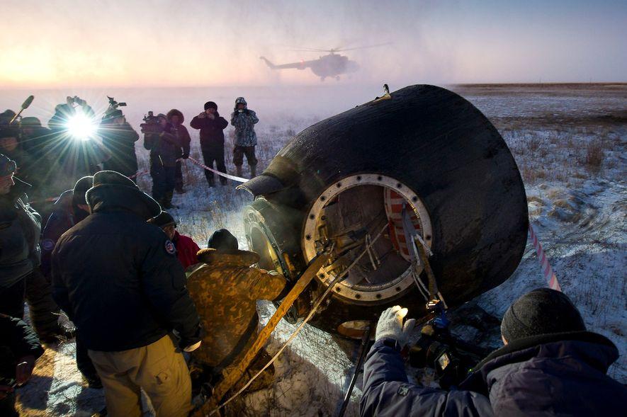 El personal de apoyo ayuda a los pasajeros de la Soyuz TMA-02M —el astronauta de la ...