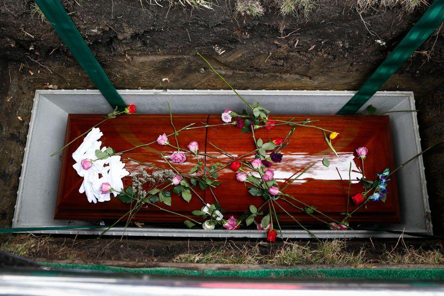 Los familiares y seres queridos arrojan rosas, la flor favorita de Lola, sobre su ataúd al ...