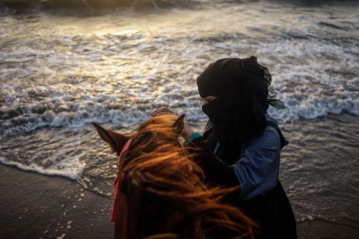 Una mujer tranquiliza a un caballo