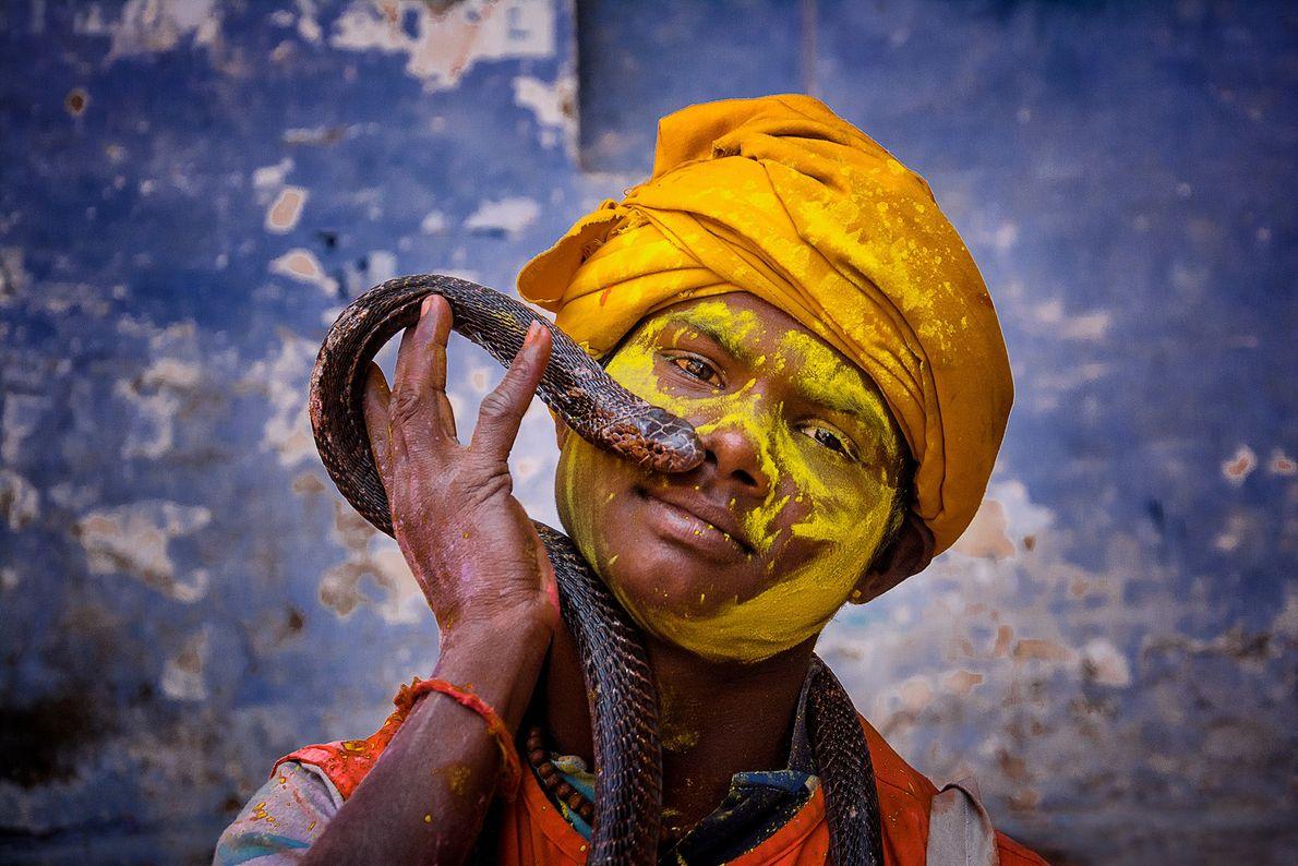 Imagen de un niño indio celebrando el Holi mientras sujeta una serpiente