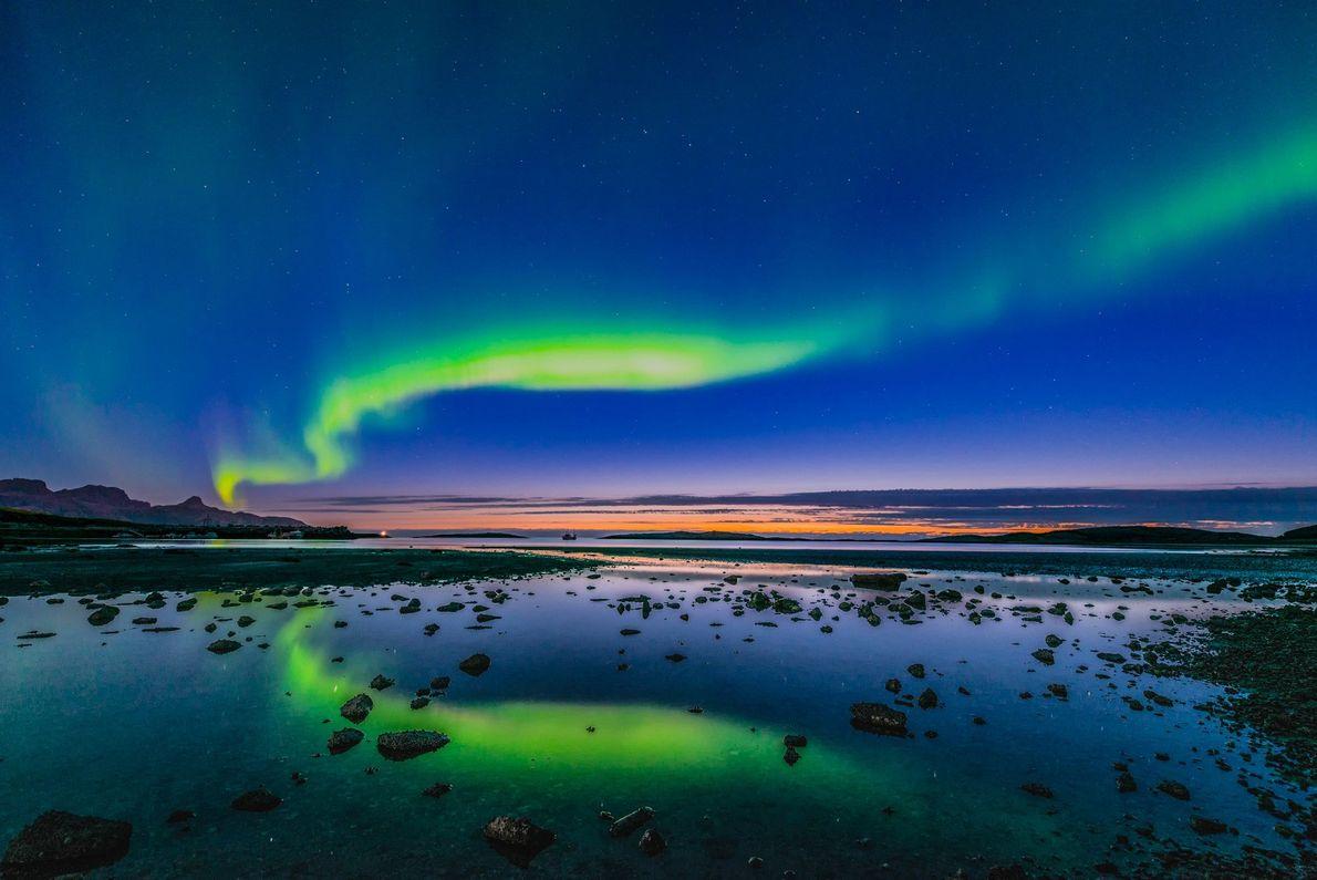 Foto de las auroras boreales en una puesta de sol sobre un lago