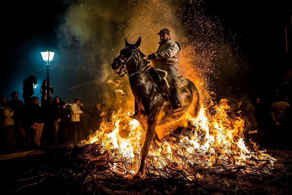 Imagen de un hombre montando un caballo a través de las llamas en España