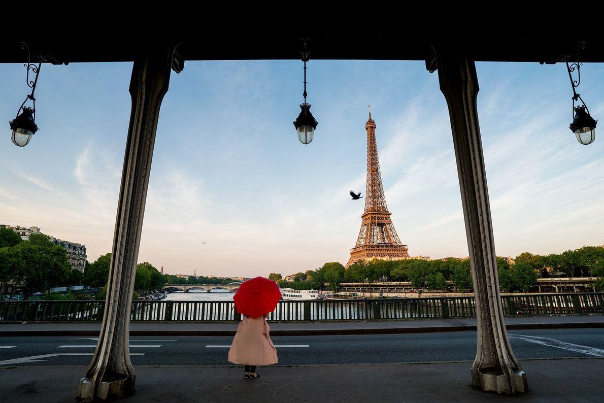 Foto de una mujer que sostiene un paraguas rojo en frente de la Torre Eiffel