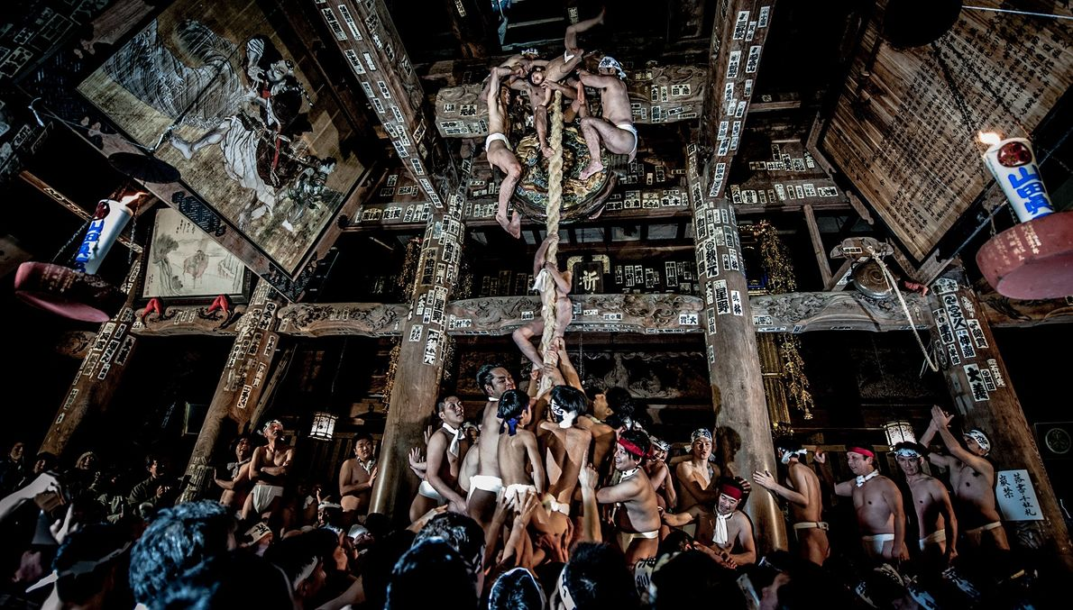 Foto de hombres sin camisa subiendo una gran cuerda dentro de un templo
