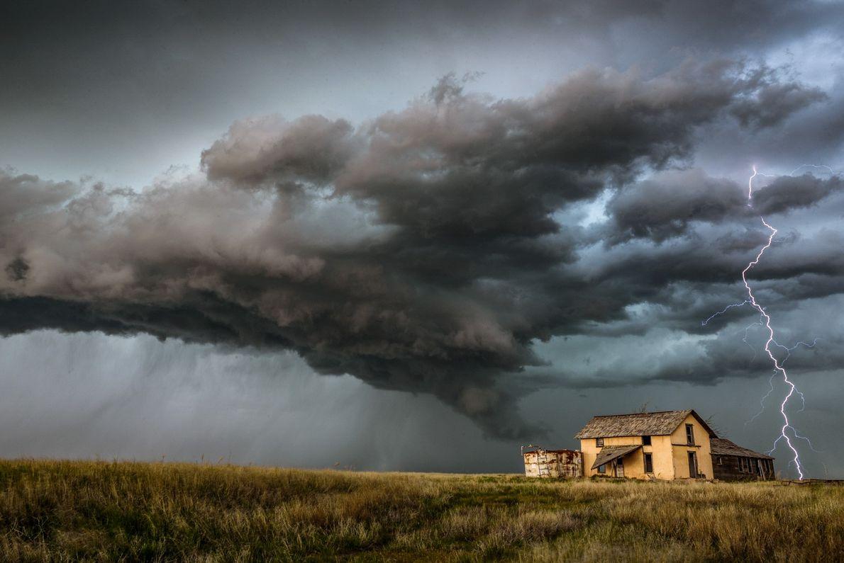 Foto de un rayo golpeando el suelo cerca de una casa