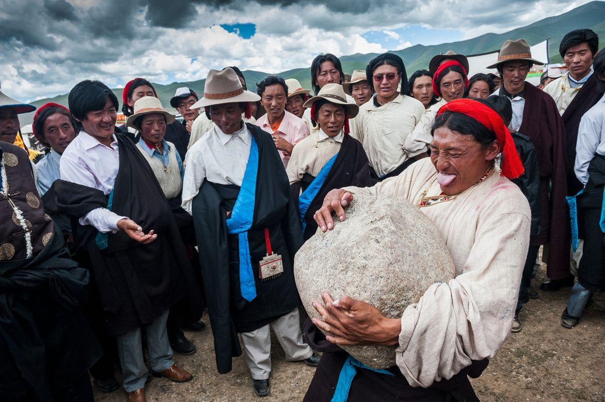 Foto de un tibetano levantando una gran roca