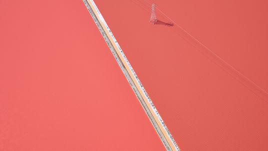 Foto de un tendido eléctrico a través de suelo de sal rosa en California