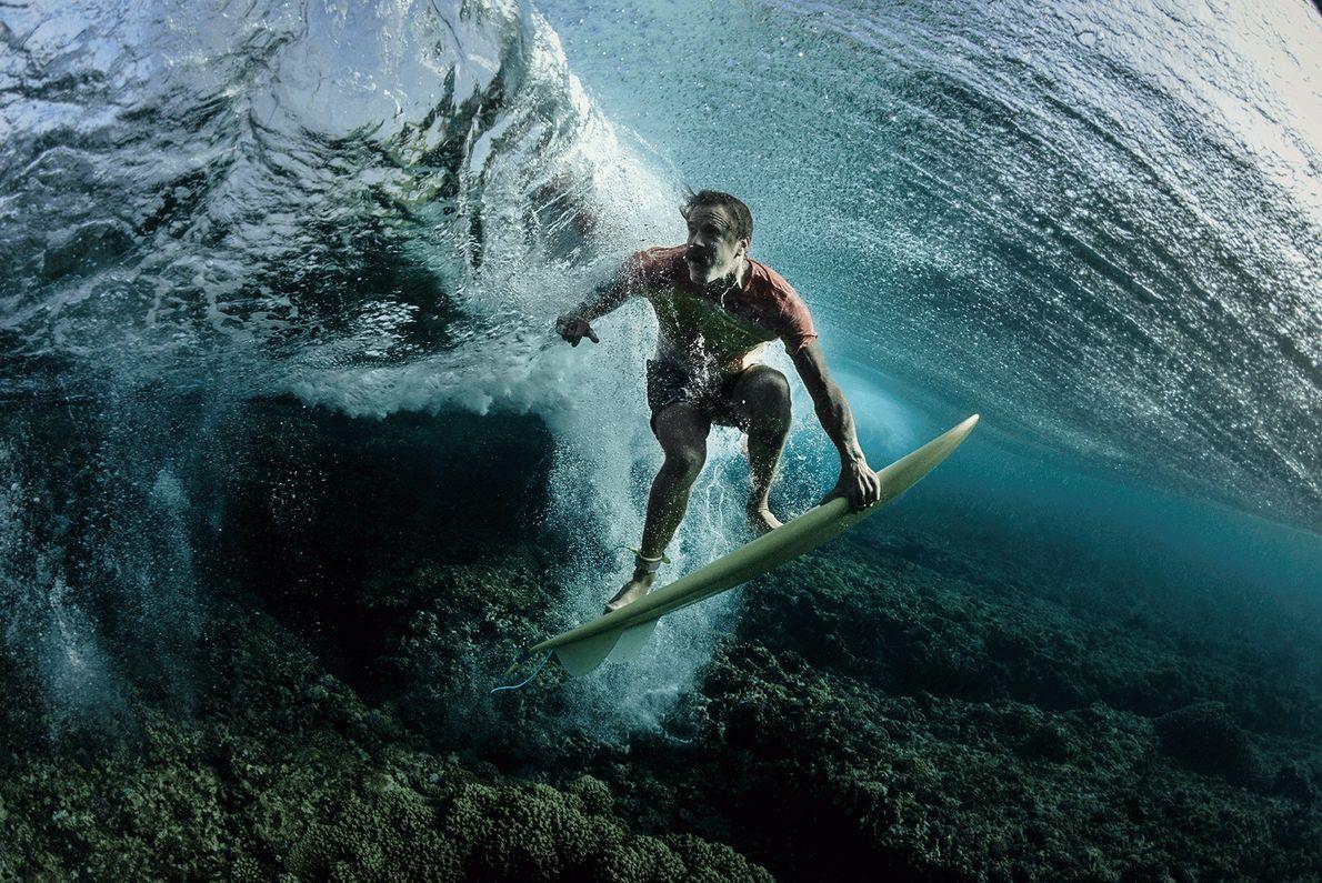 Imagen de un surfista en su tabla bajo el agua en Fiji