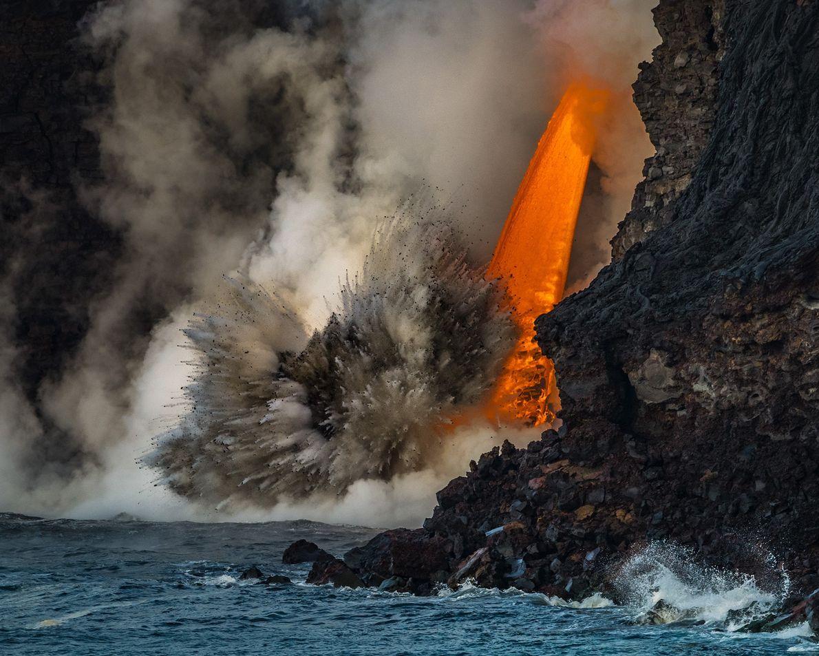 Imagen de lava cayendo al mar desde el lateral de un volcán