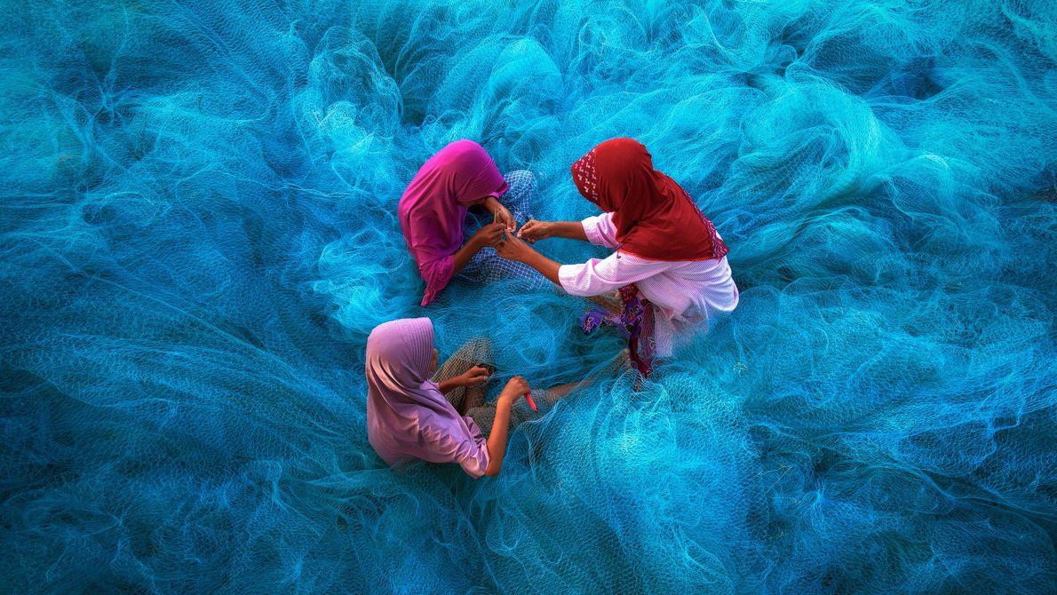 Imagen de una madre y sus hijos reparando redes de pesca azules