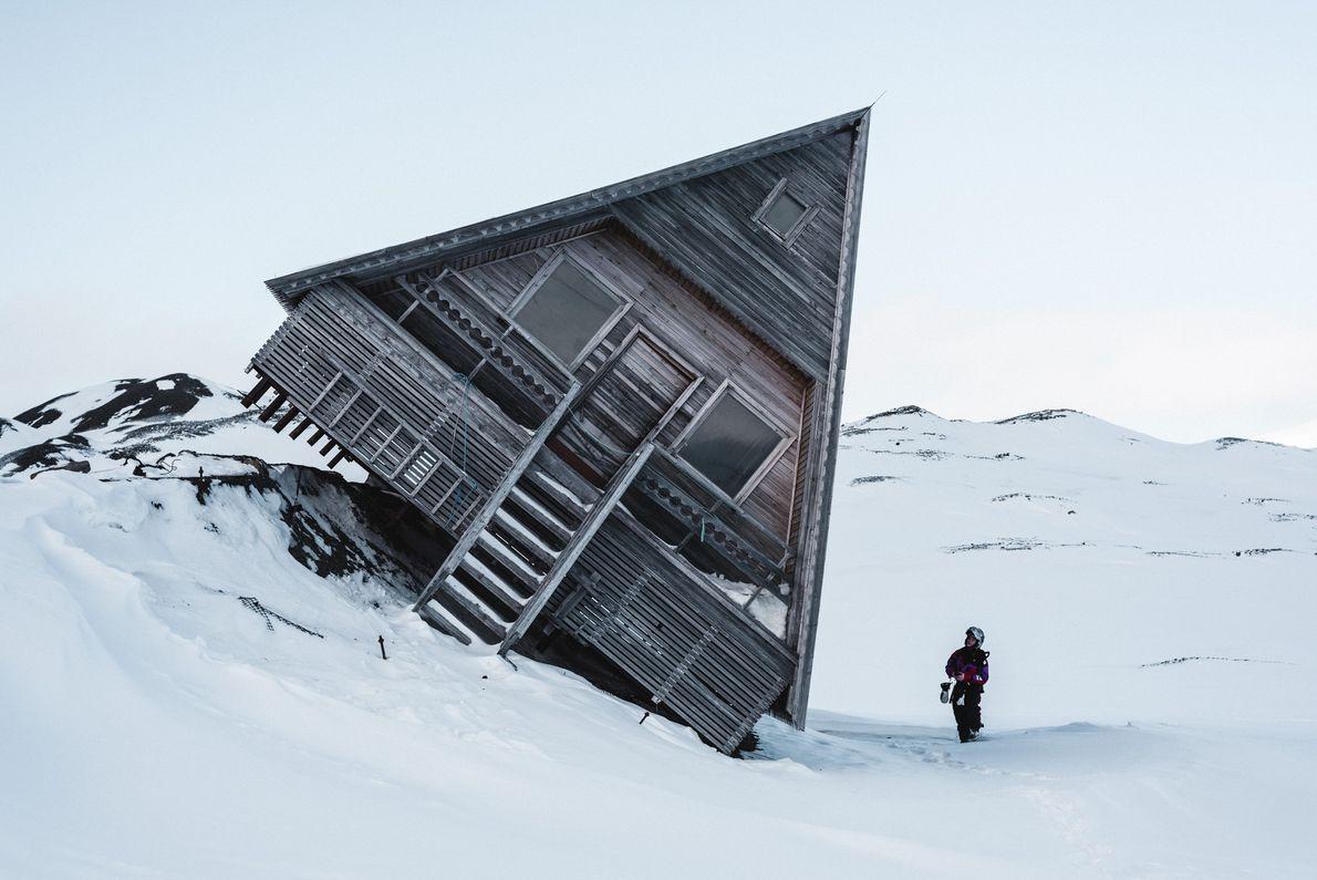 Imagen de una cabaña inclinada sobre la nieve