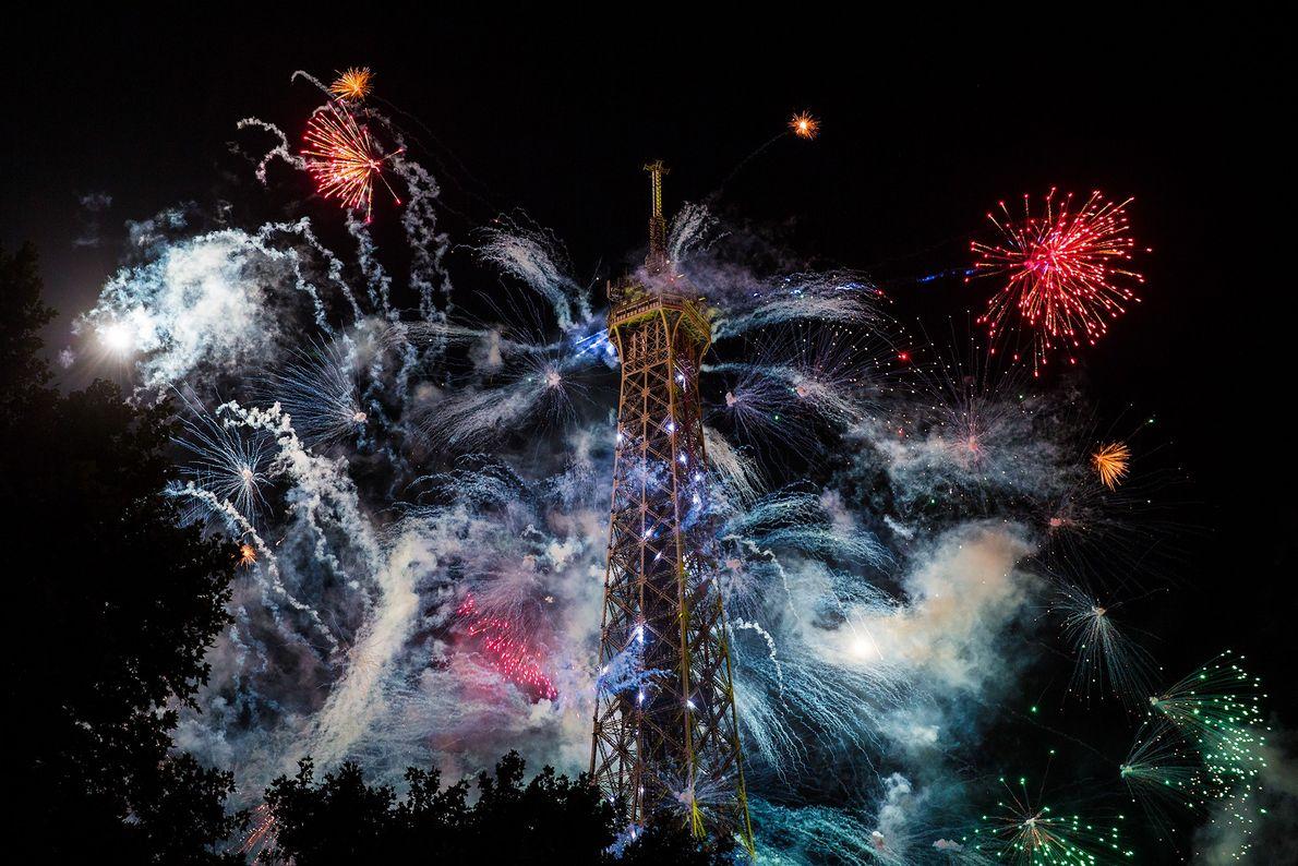 Foto de fuegos artificiales explotando detrás de la Torre Eiffel en París