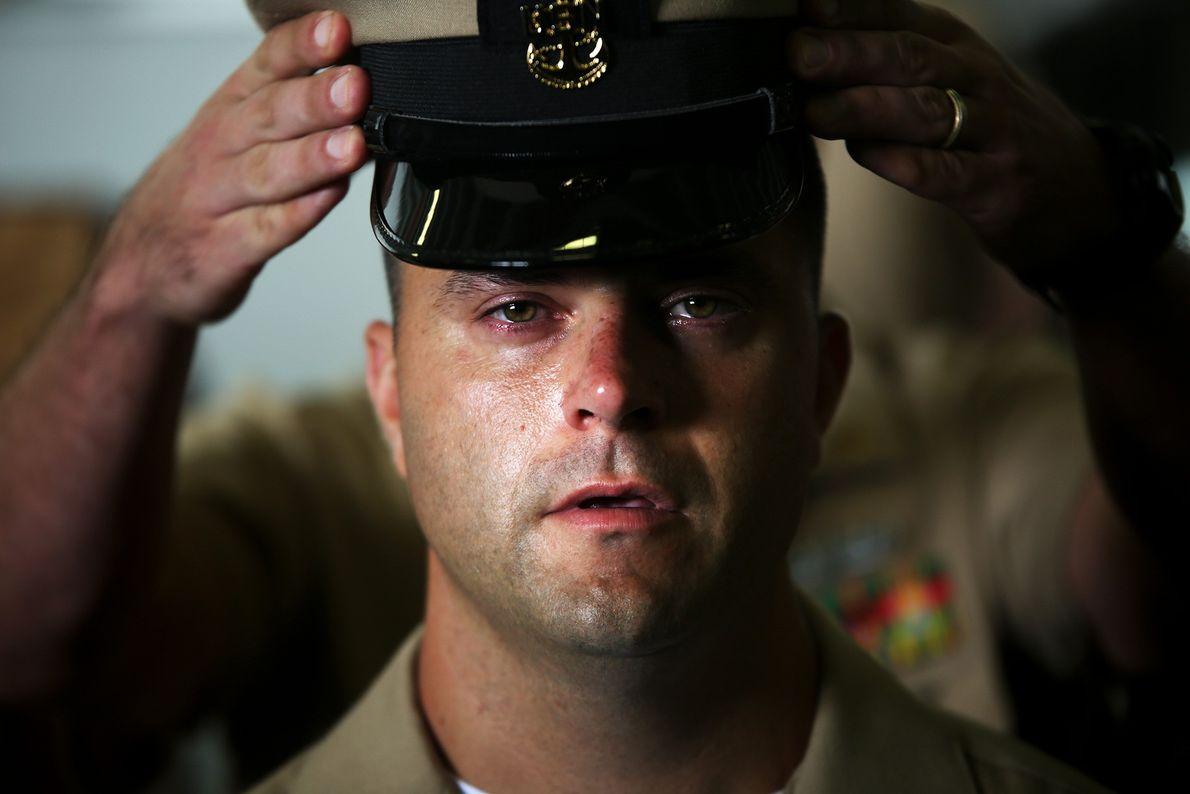 Imagen de unas manos colocando un sombrero militar en la cabeza de un hombre en la ...