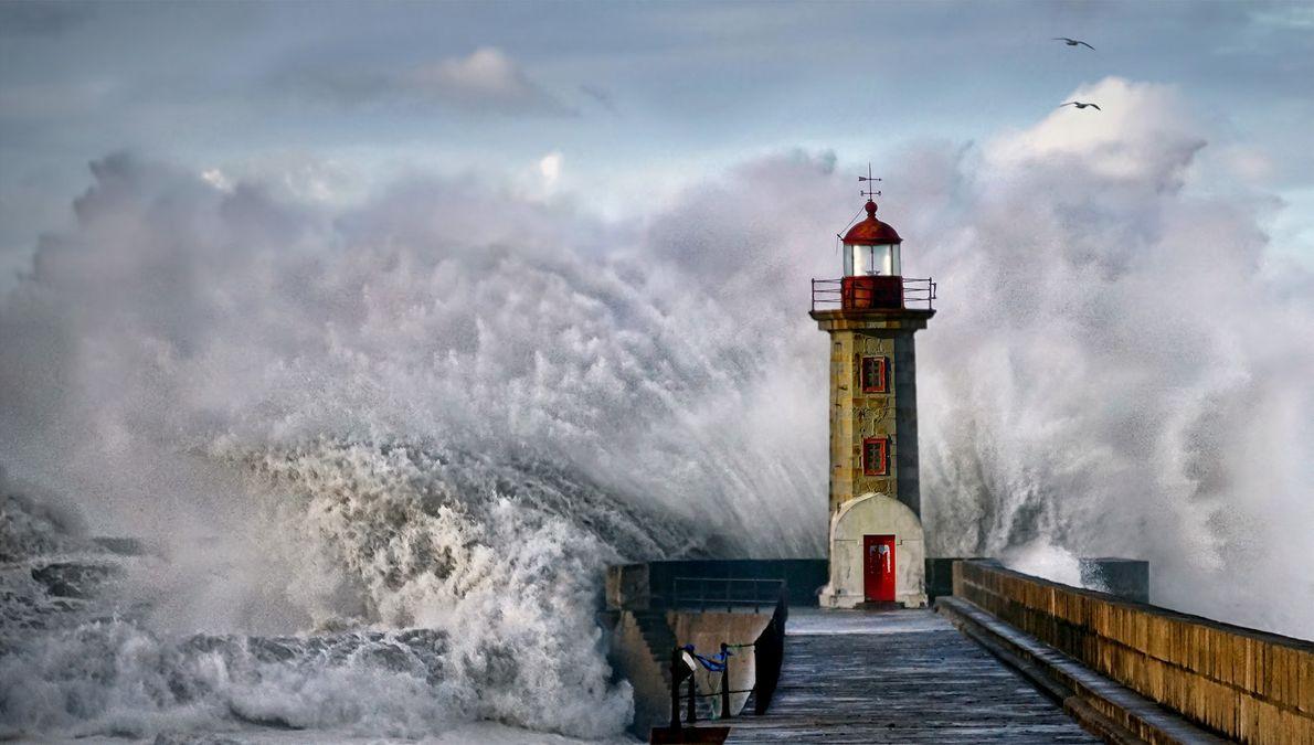 Imagen de una ola estrellándose contra un faro en Portugal