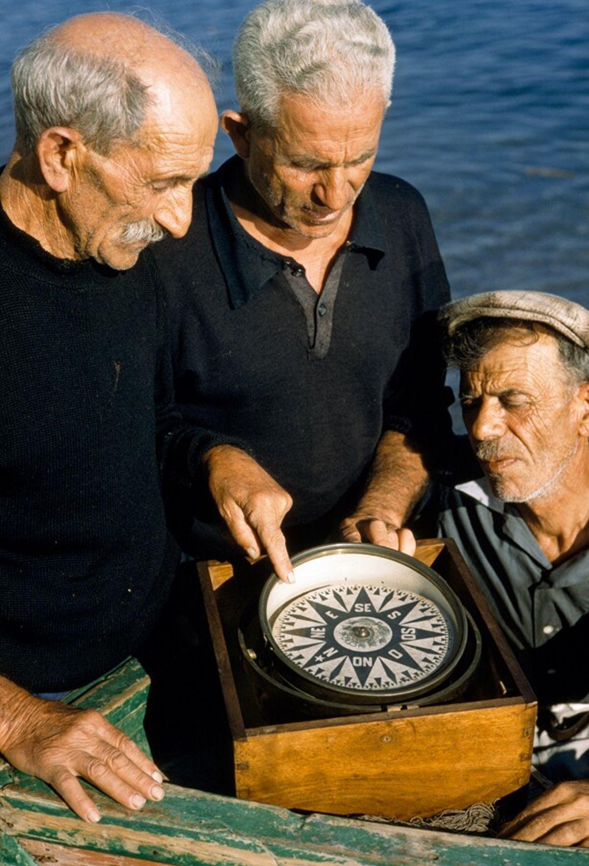 Tres pescadores observan una brújula antigua