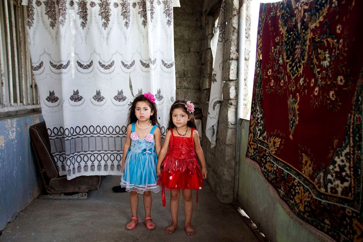 Imagen de hermanas gemelas junto a unos tapices