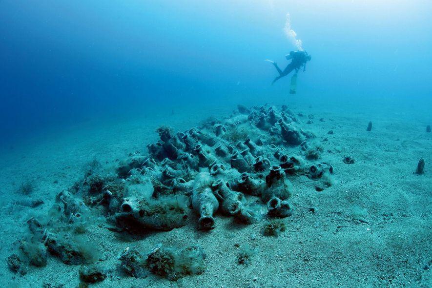En la costa de Albania, un buceador explora un cargamento de ánforas de un naufragio de ...