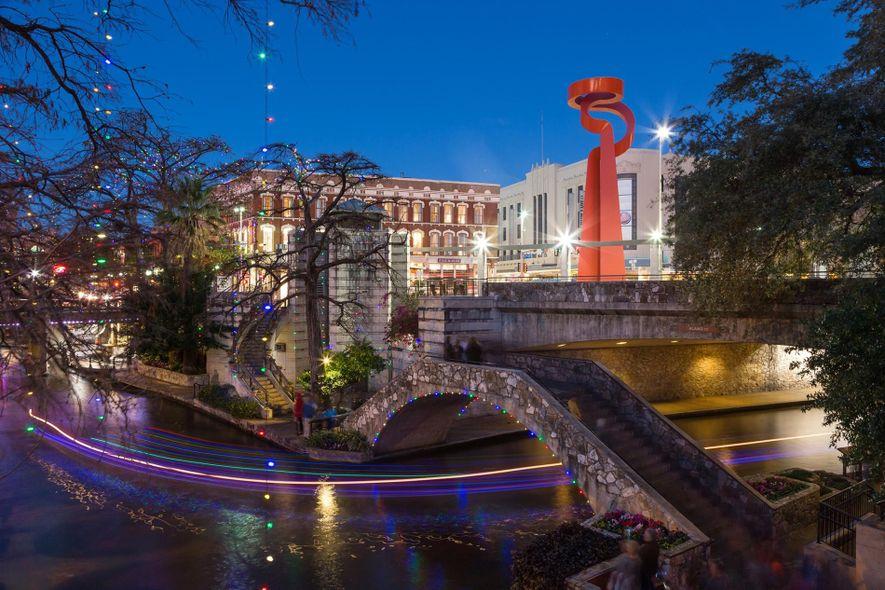 Las luces llenan de color el paseo junto al río en el centro de San Antonio, ...