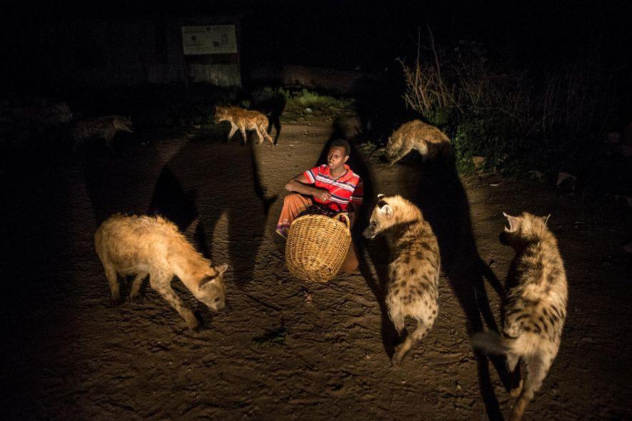 Abbas alimenta a las hienas frente a su casa en Harar, Etiopía.