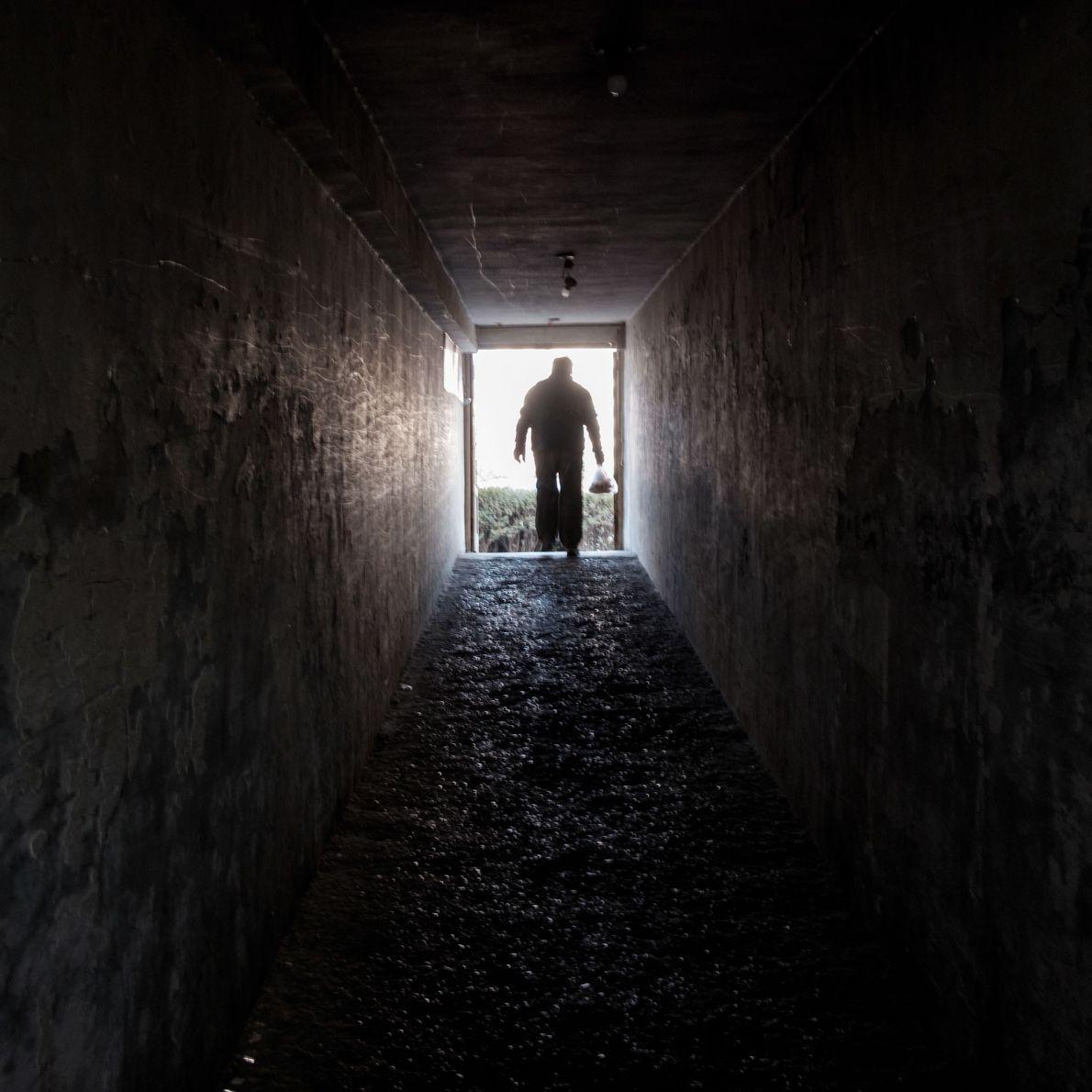 Un hombre sale de un refugio