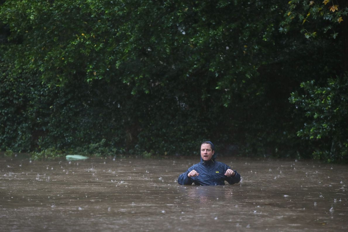 Un residente camina por una calle inundada