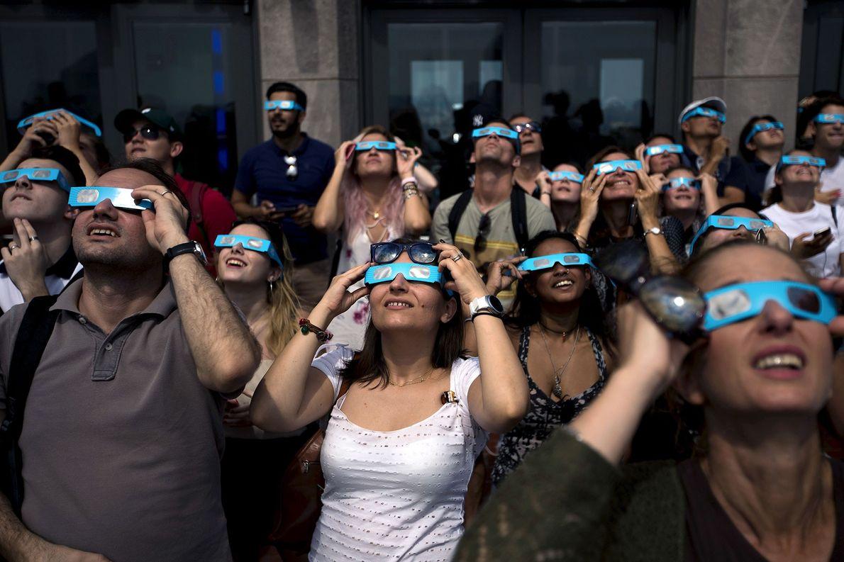 Gente contemplando el eclipse solar en el observatorio de «Top of the Rock» en el Centro …