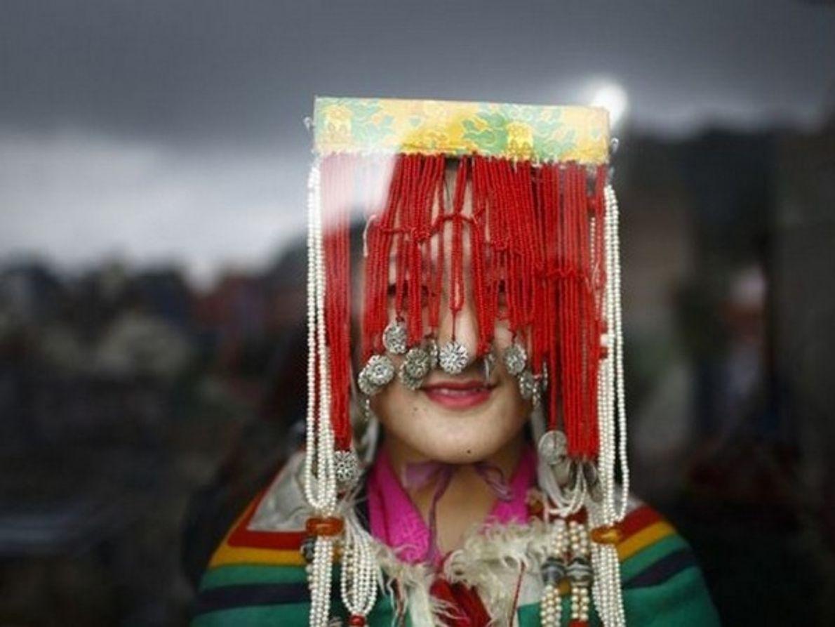 Una niña tibetana mira por la ventana de un monasterio, vestida con el traje tradicional para celebrar el 78 …