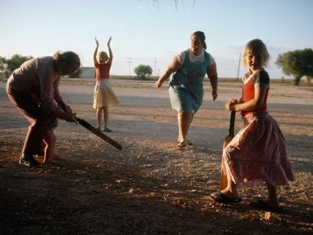 Una familia juega al cricket en una calle peatonal principal en Cooks, Australia, en 1986.