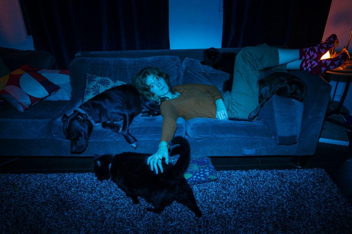 La fotógrafa Kendrick Brinson en el sofá con sus perros y sus gatos