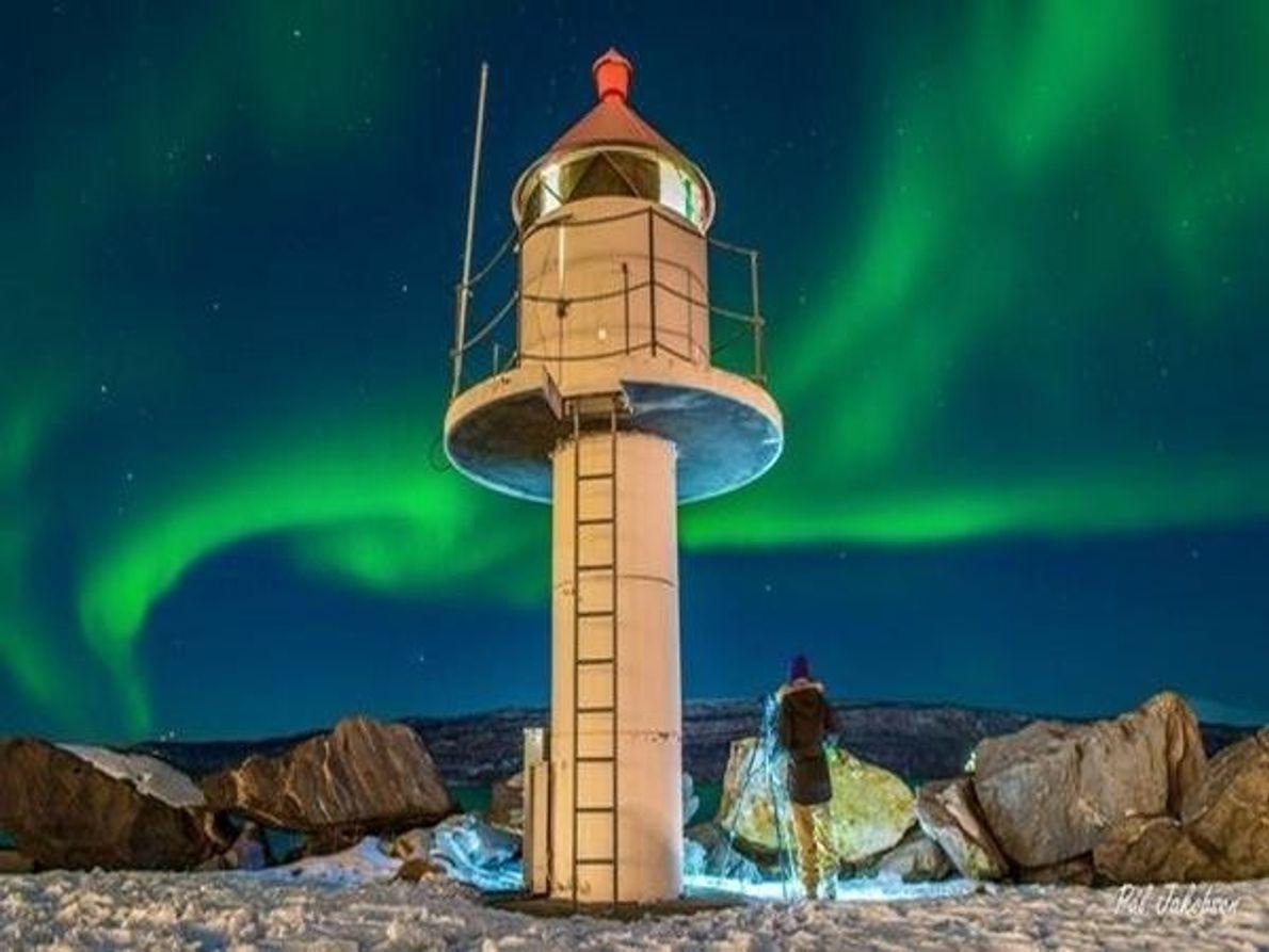 Un faro en el norte de Noruega es iluminada por el resplandor verde de la aurora boreal danzando en …