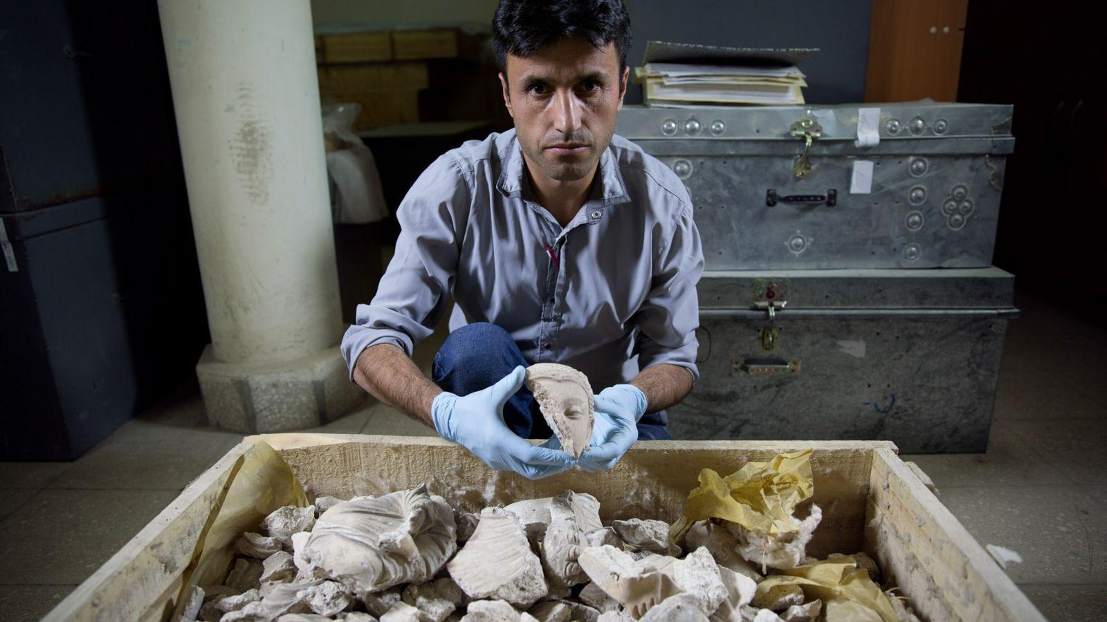 Un hombre muestra una cabeza de buda dañada