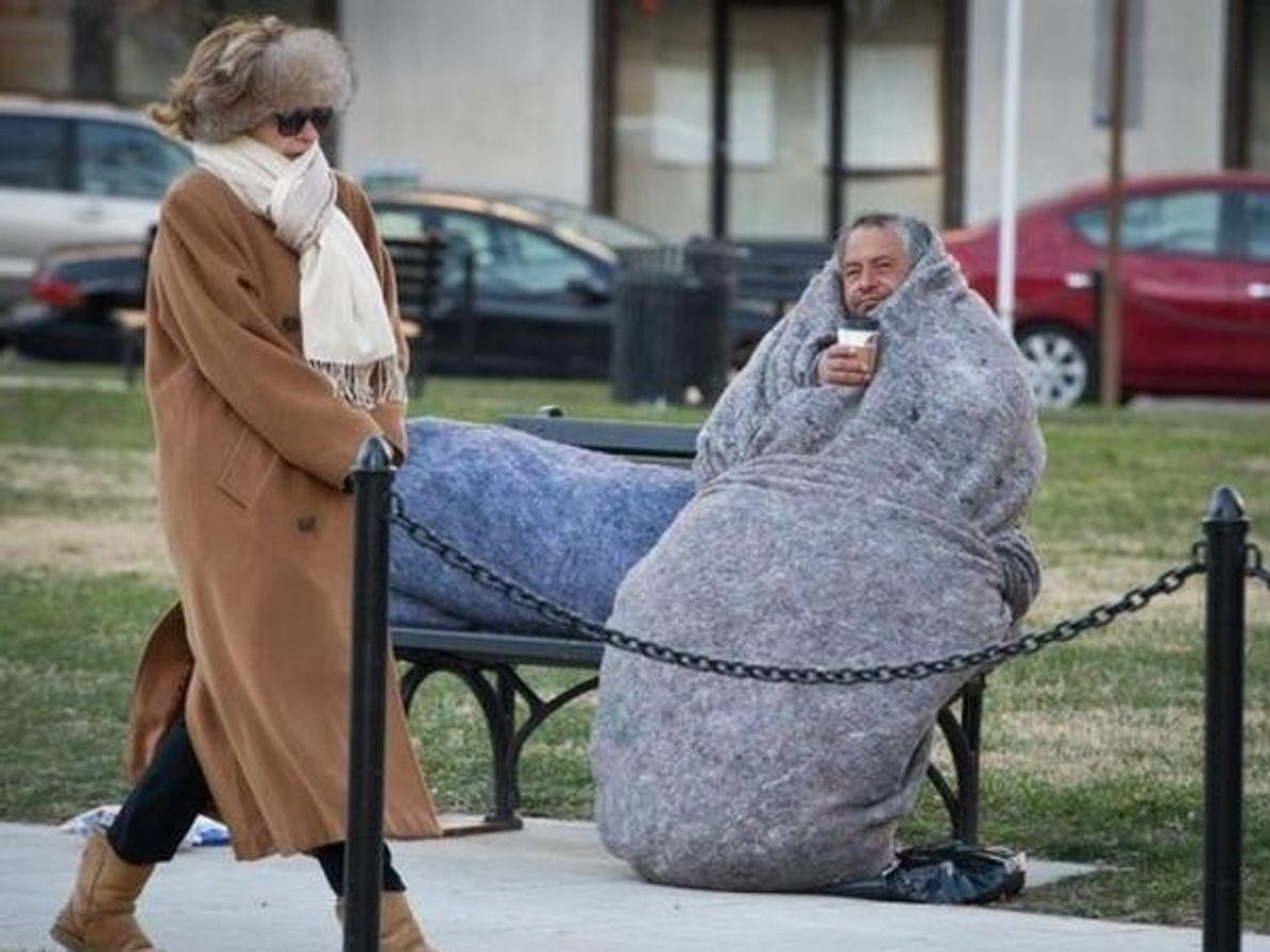 Dos ciudadanos se abrigan todo lo que pueden para protegerse de las heladas temperaturas en Washington D.C. durante …