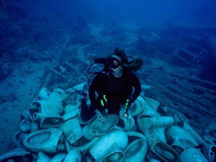 Una submarinista examina una pila de inodoros en el fondo del mar.