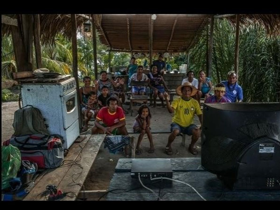 Habitantes de un remoto pueblo de la Amazonia brasileña se reúnen ante la televisión, que sufrió …