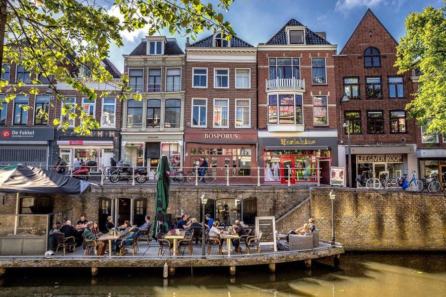 Restaurantes y tiendas se distribuyen a lo largo del antiguo muelle de un canal en Leeuwarden, ...